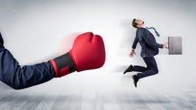 Красная перчатка бокса стучает вне маленьким бизнесменом стоковое фото