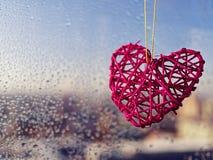 Красная плетеная смертная казнь через повешение сердца на веревочке против предпосылки стекла с падениями на солнечный день Стоковое Изображение RF