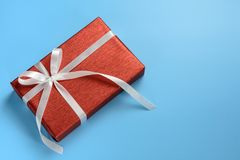 Красная подарочная коробка с белой лентой на голубой предпосылке Стоковое Изображение
