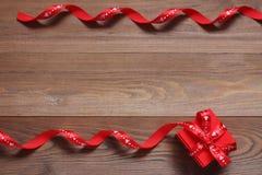 Красная подарочная коробка с бюрократизмами на деревянной предпосылке Стоковое Фото