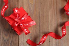Красная подарочная коробка с лентой на деревянной предпосылке Стоковые Фото
