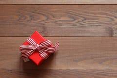 Красная подарочная коробка с лентой на деревянной предпосылке Стоковые Изображения