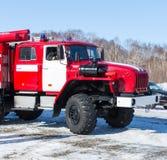 Красная пожарная машина на столбе около древесины в зиме Стоковая Фотография