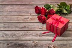 Красная подарочная коробка с смычком и букетом красных роз на деревянном backgroun Стоковое Фото