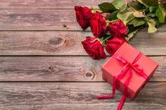 Красная подарочная коробка с смычком и букетом красных роз на деревянном backgroun Стоковые Фото