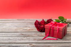 Красная подарочная коробка с смычком и букетом красных роз на деревянном backgroun Стоковая Фотография