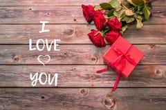 Красная подарочная коробка с смычком и букетом красных роз на деревянном backgroun Стоковое фото RF