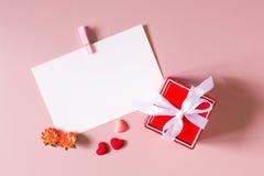 Красная подарочная коробка с смычком, шаблоном канцелярских принадлежностей/фото с струбциной, малыми сердцами и весной цветет Стоковое Фото