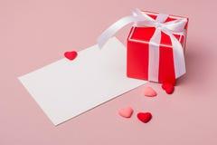 Красная подарочная коробка с смычком, шаблоном канцелярских принадлежностей/фото и малыми сердцами Стоковая Фотография RF