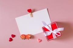Красная подарочная коробка с смычком, шаблоном канцелярских принадлежностей/фото с струбциной, малыми сердцами и весной цветет Стоковое Изображение