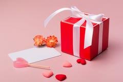Красная подарочная коробка с смычком, шаблоном канцелярских принадлежностей/фото, конфетой, цветками весны и малыми сердцами Стоковое Изображение RF