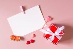 Красная подарочная коробка с смычком, шаблоном канцелярских принадлежностей/фото/открытки с струбциной, малыми сердцами, конфетой Стоковые Изображения RF