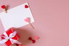Красная подарочная коробка с смычком, шаблон канцелярских принадлежностей/фото с струбциной, малые сердца и конфета Стоковые Фото