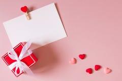 Красная подарочная коробка с смычком, шаблон канцелярских принадлежностей/фото с струбциной и малые сердца Стоковое Изображение
