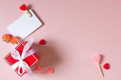 Красная подарочная коробка с шаблоном смычка, карточки кредита/посещения с струбциной, цветками весны, конфетой и малыми сердцами Стоковое Фото