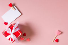 Красная подарочная коробка с шаблоном смычка, карточки кредита/посещения с струбциной, конфетой и малыми сердцами Стоковая Фотография RF