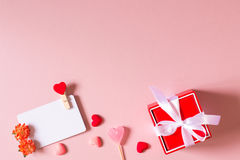 Красная подарочная коробка с шаблоном смычка, карточки кредита/посещения с струбциной, цветками весны, конфетой и малыми сердцами Стоковые Изображения RF