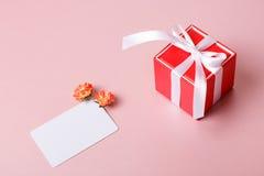 Красная подарочная коробка с шаблоном смычка, карточки кредита/посещения и цветками весны Стоковые Изображения RF