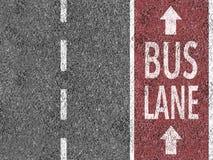 Красная полоса для движения автобусов на асфальте Стоковая Фотография RF