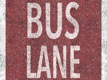 Красная полоса для движения автобусов на асфальте Стоковые Изображения RF