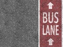 Красная полоса для движения автобусов на асфальте Стоковое фото RF