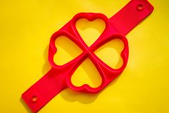 Красная прессформа силикона на желтой предпосылке Кольцо яичка формы сердца силикона для сковороды Жарить яичко с формой силикона Стоковое Изображение