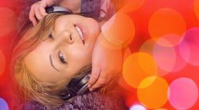 Красная предпосылка музыки и музыка милой молодой женщины слушая, смотря камеру Стоковые Фото
