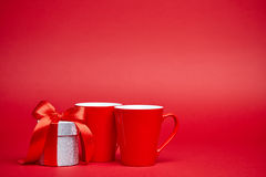 Красная предпосылка с подарком и кружками Стоковое Фото