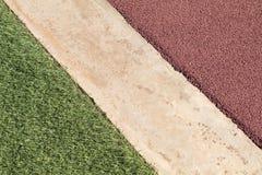 Красная резиновая поверхность пола спортивной площадки Wetpour рядом с бетоном и Стоковое фото RF