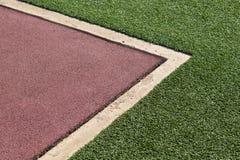 Красная резиновая поверхность пола спортивной площадки Wetpour рядом с бетоном и Стоковые Изображения