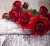 красная роза на газете Стоковое Изображение