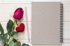 Красная роза с карандашем и пустой тетрадью на деревянной предпосылке Стоковые Фотографии RF