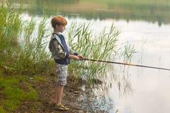 Красная рыбная ловля мальчика волос в озере Стоковые Изображения