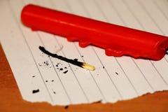 Красная свеча с, который сгорели спичкой на растрепанной бумаге Стоковая Фотография RF
