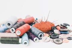 Красная связанная пусковая площадка иглы для шить, шить кнопок и покрашенных катушек потока на белой предпосылке с космосом экзем стоковое фото