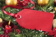 Красная смертная казнь через повешение бирки подарка на рождественской елке с украшениями, космосе экземпляра Стоковое фото RF