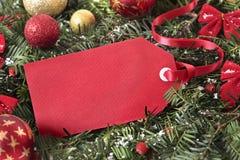 Красная смертная казнь через повешение бирки подарка на рождественской елке с украшениями, космосе экземпляра Стоковые Изображения RF