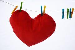 Красная смертная казнь через повешение сердца на веревке для белья на белой предпосылке Стоковое Изображение
