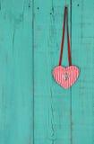 Красная смертная казнь через повешение сердца лентой на предпосылке teal голубой деревянной Стоковая Фотография