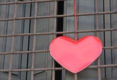 Красная смертная казнь через повешение сердца на решетке окна вне здания дальше Стоковые Изображения RF