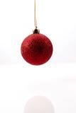 Красная смертная казнь через повешение шарика рождества в midair против белой предпосылки Стоковое Изображение