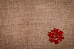 Красная снежинка на мешковине Стоковые Изображения
