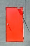 Красная современная дверь с серой стеной цемента Стоковые Фотографии RF