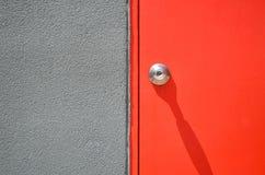 Красная современная дверь с серой стеной цемента Стоковое фото RF