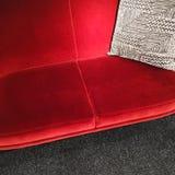 Красная софа бархата с серым орнаментальным валиком Стоковые Изображения