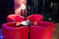 Красная софа вокруг малой таблицы в освещении ночного клуба от лампы Стоковые Фотографии RF