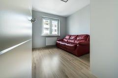 Красная софа в пустой комнате Стоковые Фотографии RF