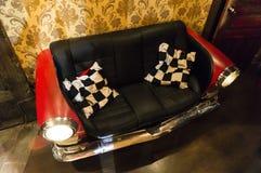 Красная софа любит автомобиль на котором светотеневые подушки Стоковое Изображение