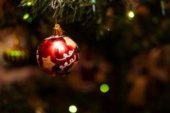 Красная стеклянная безделушка на искусственной рождественской елке Стоковые Изображения