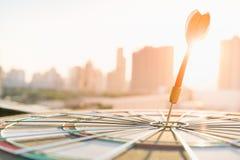 Красная стрелка дротика ударяя в центре цели dartboard с современной предпосылкой города и захода солнца Стоковые Фото